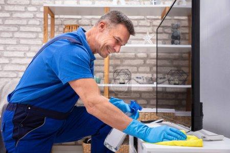 Photo pour Happy Man portant des gants de nettoyage de meubles avec bouteille de pulvérisation et serviette - image libre de droit