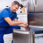 Mature Male Serviceman Repairing Refrigerator With...
