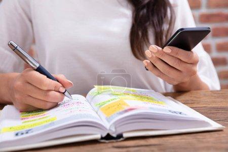 Photo pour Gros plan d'une femme d'affaires tenant le calendrier d'écriture de téléphone portable dans le journal avec stylo - image libre de droit