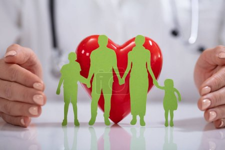 Photo for Doctor's Hand Protecting Green Family Paper Cut Out With Red Heart Shape On Desk - Royalty Free Image