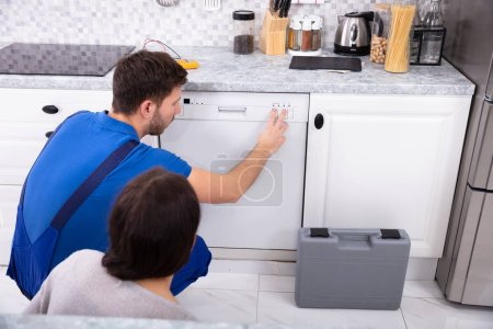 Photo for Serviceman Crouching On Kitchen Floor Pressing Button Of Dishwasher While Woman Looking At Him - Royalty Free Image