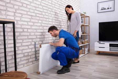 Photo pour Jeune réparateur installant le radiateur sur le mur de brique avec la femme debout à la maison - image libre de droit