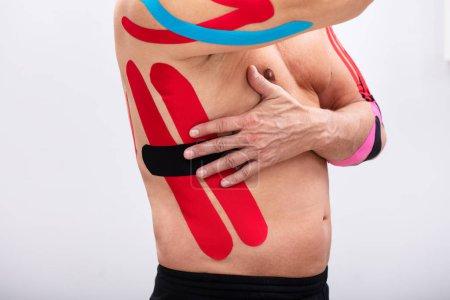 Photo pour L'homme qui applique la kinésiologie rouge et noire tapote sur ses côtes. La forme du corps a été modifiée lors de la retouche - image libre de droit