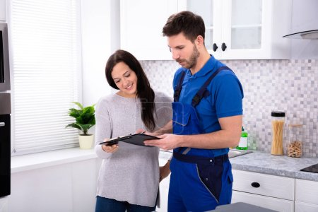 Photo pour Gros plan de jeune plombier mâle montrant facture à femme dans la cuisine - image libre de droit