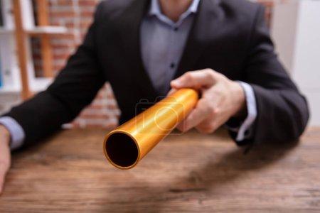 Photo pour Section médiane de la main d'une personne maintenant relais or Baton au dessus de bureau en bois - image libre de droit