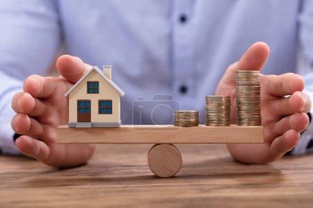 Photo pour Modèle de petite maison et pièces d'or empilées en équilibre sur une balançoire en bois - image libre de droit