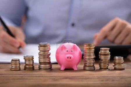 Photo pour Des pièces empilées et une tirelire rose devant un homme d'affaires calculant la facture sur un bureau en bois - image libre de droit