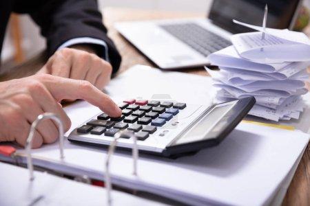 Photo pour Gros plan de la main de l'homme d'affaires à l'aide de calculatrice lors du calcul de la facture sur le bureau - image libre de droit