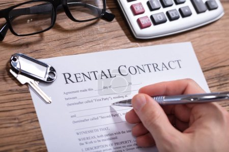 Photo for Close-up Of Key Over A Person's Hand Filling Rental Contract Form - Royalty Free Image