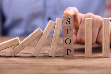 Photo pour Doigt de l'homme d'affaires sur les blocs en bois avec arrêt du texte arrêtant Dominos tombant sur le bureau en bois - image libre de droit