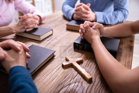 Photo for Close-up Of Businesspeople's Praying Hands Over The Bible On Wooden Desk - Royalty Free Image