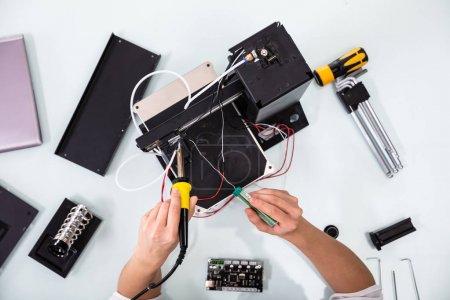 Photo pour Jeune technicienne portant des lunettes de sécurité à l'aide de fer à souder - image libre de droit