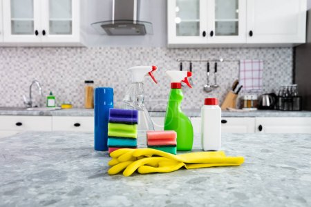Photo for Close-up Of Cleaning Supplies And Yellow Handgloves On The Kitchen Countertop - Royalty Free Image