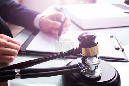 Judge Writing On Legal Documents With Mallet And S...