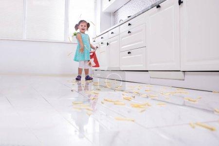 Photo pour Fille de sourire jetant Français frites dans la cuisine - image libre de droit