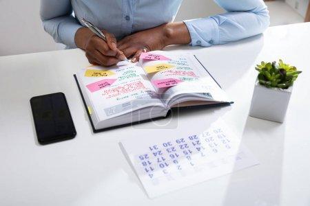 Photo pour Calendrier de vérification de main de femme d'affaires dans le journal avec le calendrier sur le bureau blanc - image libre de droit
