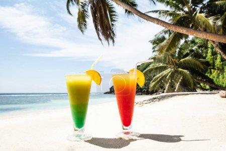 Photo pour Gros plan de verres à cocktail colorés sur la plage de sable - image libre de droit