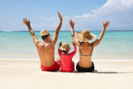 Photo for Rear View Of Family Sitting On Sand Raising Their Hands Enjoying On The Beach - Royalty Free Image