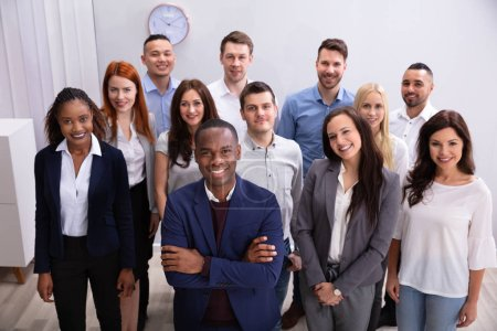 Photo for Group Of Young Successful Multi-ethnic Businesspeople Standing In Office Looking At Camera - Royalty Free Image