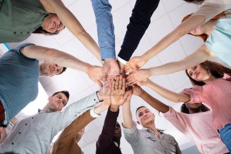 Photo pour Groupe multi-ethnique de personnes empilant la main montrant l'unité - image libre de droit