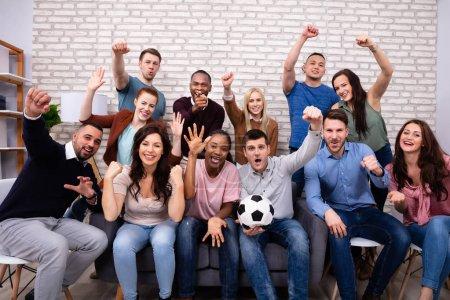 Photo pour Amis multiraciaux excités assis sur le canapé regardant le match de football à la maison - image libre de droit