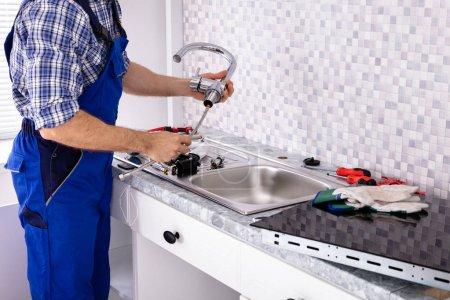 Mid Section Of Male Installateur Montage der Küchenspüle Wasserhahn
