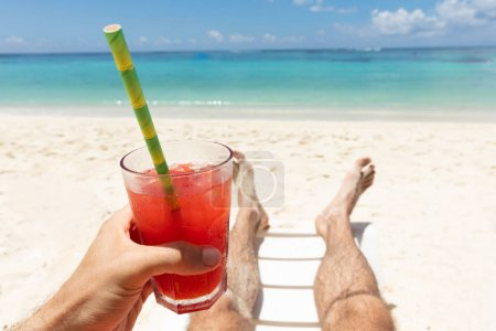 Photo for Close-up Of A Man Lying On Beach Holding Glass Of Red Juice In Hand - Royalty Free Image