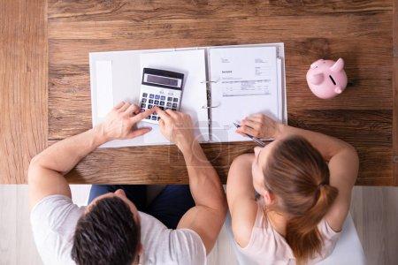 Photo pour Une vue aérienne du couple calculant la facture fiscale à l'aide d'une calculatrice sur un bureau en bois à la maison - image libre de droit