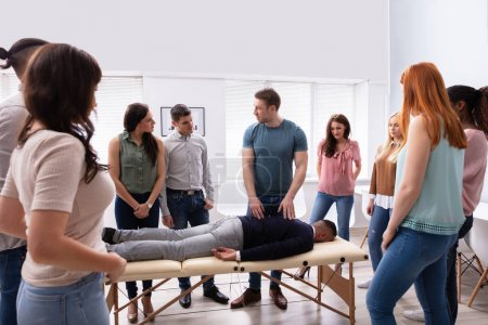 Photo pour Instructeur masculin enseignant la technique de massage au groupe de personnes multi-ethniques - image libre de droit