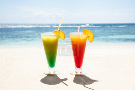 Two Glasses Of Colorful Cocktails On The Sandy Beach Against Blue Sky