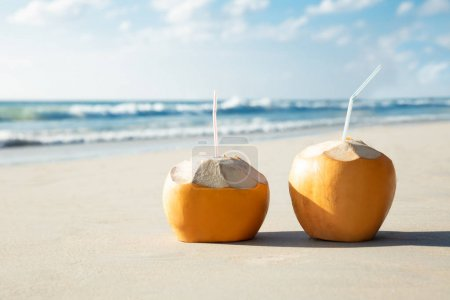 Photo for Close-up Of Two Coconuts With Drinking Straw On Sand At Beach - Royalty Free Image