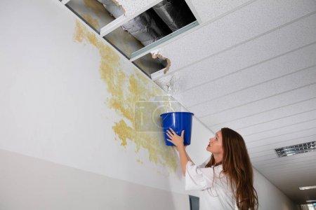 Photo pour Femme inquiète tenant un seau bleu sous le plafond de fuite dans le couloir - image libre de droit