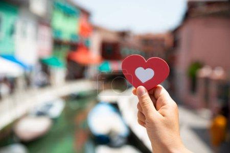 Photo pour Gros plan d'un touriste tenant la forme d'un cœur rouge contre des maisons floues à Venise - image libre de droit