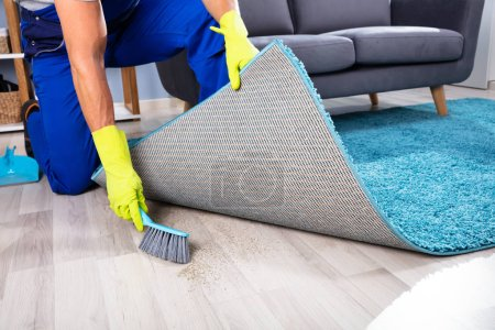 Photo for Low section View Of A Lazy Janitor Sweeping Dirt Under The Carpet - Royalty Free Image