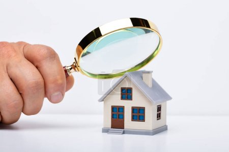 Photo pour Gros plan de la main d'une personne tenant du verre grossissant sur une maison miniature sur la table - image libre de droit