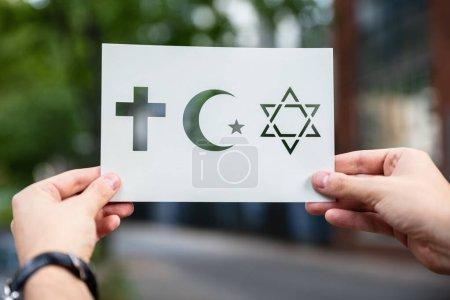 Photo pour Mains tenant du papier avec des symboles de religion découpés à l'extérieur - image libre de droit