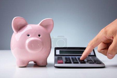 Photo pour Gros plan de la personne calculant avec la calculatrice près de la tirelire rose au bureau blanc - image libre de droit