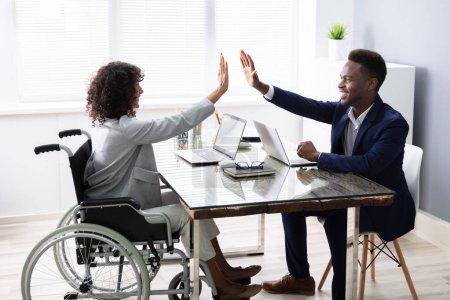 Photo pour Femme d'affaires handicapée donnant High Five à son partenaire au bureau - image libre de droit