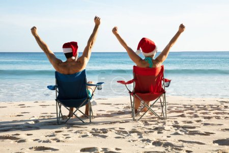 Photo for Rear View Of A Young Couple With Santa Hats Sitting On Chair Raising Their Arms - Royalty Free Image