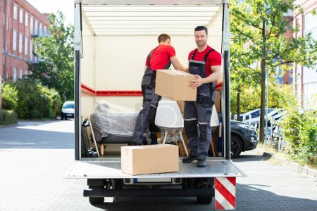 Photo for Two Young Men Unloading And Stacking The Brown Cardboard Boxes On Moving Truck - Royalty Free Image