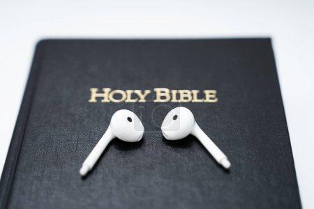 Photo pour Photo de écouteurs sans fil blancs sur le livre biblique - image libre de droit