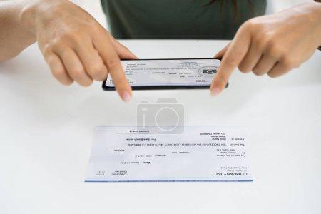 Photo pour Femme prenant des photos de chèque pour faire un dépôt à distance à la banque - image libre de droit