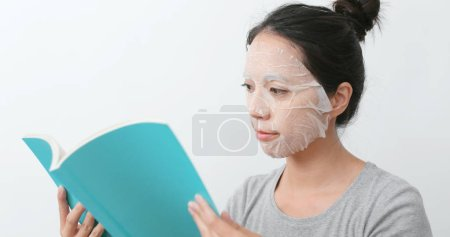 Woman apply paper mask and read book