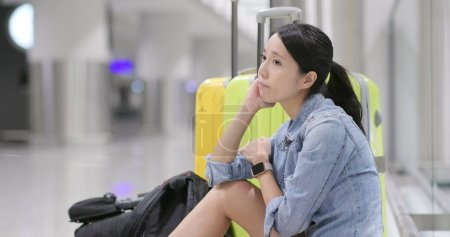 Woman wait so long for the flight transit and yawning at the airport carry with backpack and luggage