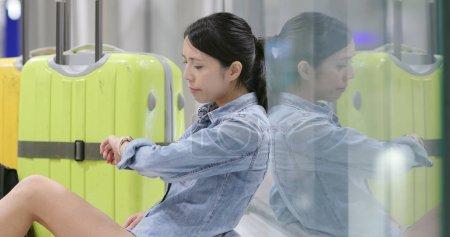 Photo pour Femme assise sur le sol avec ses bagages et sac à dos à l'aéroport, attendant pour le transport en vol - image libre de droit