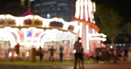 Photo for Blur view of carousel in amusement park in the evening - Royalty Free Image