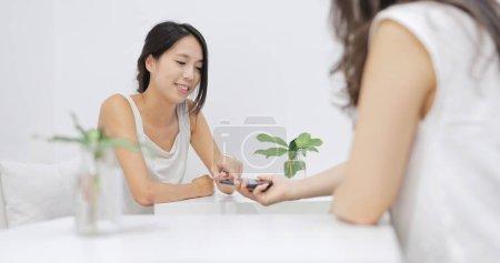 Photo pour Des amies parlent dans un café et regardent le téléphone portable ensemble - image libre de droit