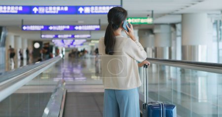 Woman talking on cellphone in airport