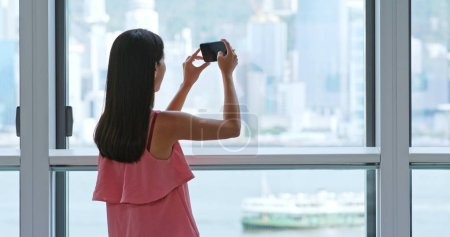 Woman taking photo out of window in Hong Kong