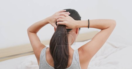 Woman tied her hair at home